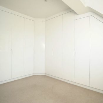 Fitted white glossy wardrobe for angled ceiling