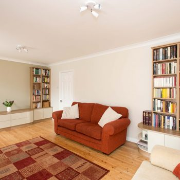 Custom fitted living room furniture with rounded worktops and open bookshelves